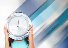 Woman holding clock in front of diagonal stripes effect Stock Images