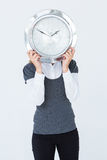 Woman holding clock in front of her head Royalty Free Stock Photo