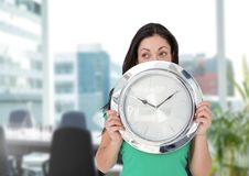 Woman holding clock in front of office Stock Image