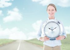 Woman holding clock in front of road Royalty Free Stock Photos