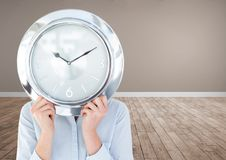 Woman holding clock in front of room Royalty Free Stock Photo