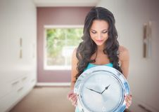 Woman holding clock in front of room window Stock Photo