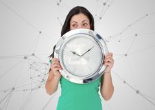 Woman holding clock in front of scientific connections Royalty Free Stock Image