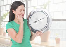 Woman holding clock in front of windows Royalty Free Stock Photo