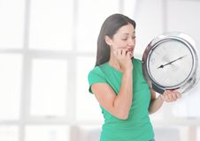 Woman holding clock in front of windows Stock Image