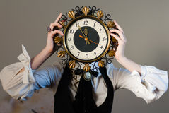 Five to Twelve Face clock. A girl holding a clock in the head, on a gray wall background Stock Photo