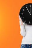 Woman holding a clock over face Stock Photos