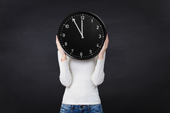 Woman holding a clock over face Royalty Free Stock Photography