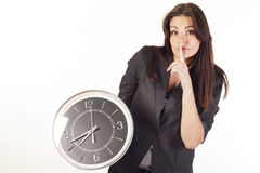Woman holding clock saying shh Stock Photos