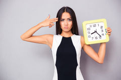 Woman holding clock and showing gun gesture to her head Stock Photography