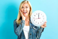 Woman holding clock showing nearly 12 Stock Photography
