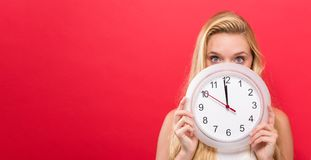 Woman holding clock showing nearly 12 Royalty Free Stock Photography