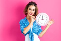 Woman holding clock showing nearly 12 Stock Images
