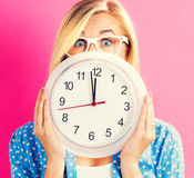 Woman holding clock showing nearly 12 Stock Image