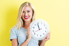 Woman holding clock showing nearly 12 Royalty Free Stock Images