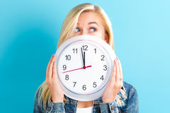 Woman holding clock showing nearly 12 Royalty Free Stock Image