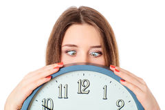 Woman holding clock  with wondering eyes foolishly. Royalty Free Stock Image