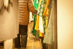 Woman holding clothes in a store during shopping. Customer holding clothes in a store during shopping or sales Stock Photography