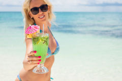 Woman holding cocktail on the beach Stock Image