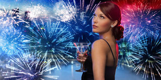 Woman holding cocktail over firework in city Royalty Free Stock Images