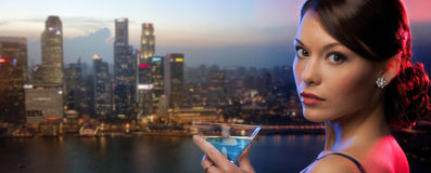 Woman holding cocktail over singapore night city Stock Images