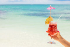 Woman holding cocktail on tropical beach Stock Image