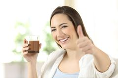 Woman holding a cocoa drink looking at camera. Happy woman holding a cocoa drink on a glass looking at camera sitting on a couch in the living room at home Stock Image