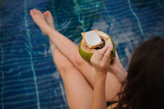 Woman holding coconut . Female legs in pool water Stock Image