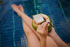Woman holding coconut . Female legs in pool water Royalty Free Stock Photography