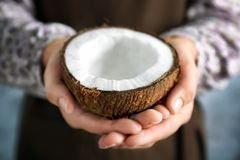 Woman holding coconut half. Closeup Stock Photography