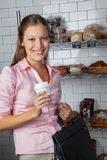 Woman Holding Coffee Cup And Bag At Store Royalty Free Stock Photo
