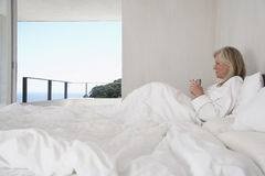 Woman Holding Coffee Cup On Bed Stock Photos