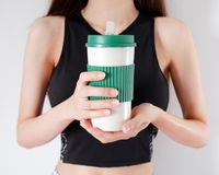 Woman holding a coffee cup in hands with exercises girls background. Blank mug for design. royalty free stock photography