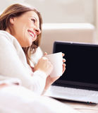 Woman holding coffee cup by laptop looking away Royalty Free Stock Photos
