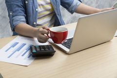 Woman holding coffee cup and newspaper with laptop computer, cal Royalty Free Stock Images