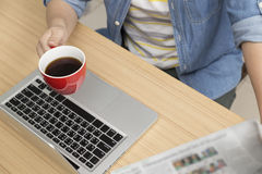Woman holding coffee cup and newspaper with laptop computer Royalty Free Stock Image
