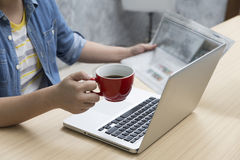 Woman holding coffee cup and newspaper with laptop computer Stock Image