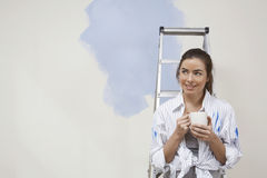 Woman Holding Coffee Cup Next To Stepladder Against Unrenovated Wall Stock Image
