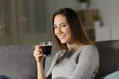 Woman holding coffee cup in the night looking at you. Sitting on a couch in the living room at home Stock Image