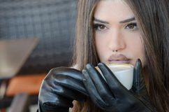 Woman holding a coffee cup, sitting in cafeteria Royalty Free Stock Image