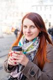 Woman holding coffee cup and smile on the blurred street. Sunny spring afternoon. Red manicure royalty free stock image