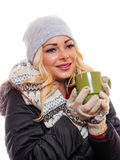 Woman holding coffee cup smiling. A happy woman is holding a cup of coffee smiling while dressed for winter royalty free stock image