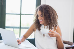 Woman holding coffee cup and using laptop in a restaurant Royalty Free Stock Photos