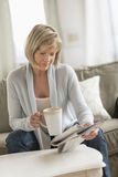 Woman Holding Coffee Mug While Reading Newspaper On Sofa Stock Images