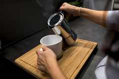 Woman holding coffee pot pouring coffee into white cup.  Royalty Free Stock Images