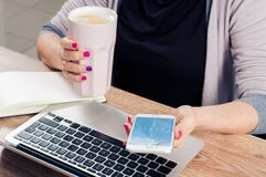 Woman holding coffee and smartphone Royalty Free Stock Photography