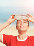 Woman holding a cold water bottle on her forehead. Eyes closed. Stock Photos