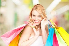 Woman holding color shopping bags in mall. Attractive woman holding color shopping bags in mall Royalty Free Stock Images