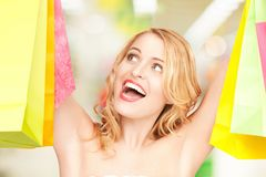Woman holding color shopping bags in mall Royalty Free Stock Images