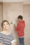 Woman Holding Color Swatches With Man Painting Wall Stock Images